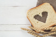 Slice of white bread with a heart carved in them and wheat ears Royalty Free Stock Photo