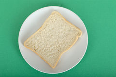 Slice of White Bread on a Plate. Against a green background Stock Images