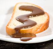 Slice of white bread watered with liquid chocolate close-up stock photo