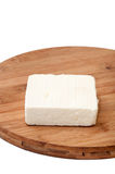 A slice of white feta cheese on a kitchen board Royalty Free Stock Images