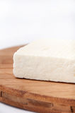 A slice of white feta cheese on a kitchen board Stock Photography