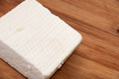 A slice of white feta cheese on a kitchen board Royalty Free Stock Image
