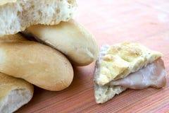 Slice of white pizza stuffed with mortadella with some bread rol. Wedge of focaccia bread stuffed with slices of bologna near some bread rolls stock photo