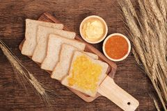 Slice whole wheat bread, butter and orange jam. Stock Image