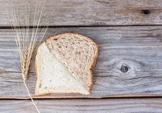 Slice of whole wheat bread and white bread melded together. Horizontal image of a white slice and a whole wheat slice of bread cut at an angle and put together Stock Image