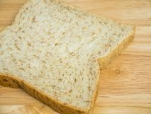 Slice whole wheat bread on wooden table Royalty Free Stock Images