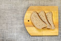 Slice whole wheat bread on wooden yellow board on natural fabric Stock Photos