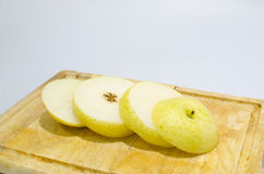 Slice yellow chinese pear on wood cutting board royalty free stock photography
