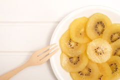 Slice of yellow kiwigold kiwi on plate. Healthy, eating and diet concept; Idea with slice of ripe yellow kiwior gold kiwi in white plate with space for text on stock images