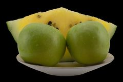 The slice of yellow watermelon and green apples on the plate. royalty free stock photography