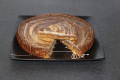 Slice of zebra cheese cake on the full cake Stock Photo