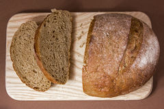 Sliced black bread on a wooden board. Black soft bread sliced on a wooden cutting board with a brown background Stock Images
