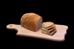 Sliced ​​bread. Bread, sliced ​​on a kitchen board. Isolated on black background Royalty Free Stock Images