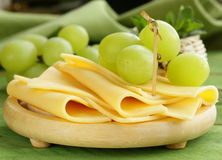 Sliced ​​cheese served on a wooden board with grapes Stock Images