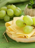 Sliced ​​cheese served on a wooden board with grapes Royalty Free Stock Photos