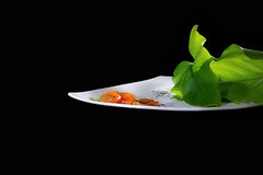 Cherry Tomatoes Salad. Creative Cuisine. Sliced cherry tomatoes with large green leaves Stock Photos