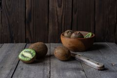 Sliced in half and whole kiwis on a wooden background royalty free stock photography