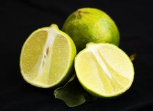 Sliced lime with leaves. On a black background stock image