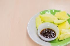 Sliced ​​mango and sweet fish sauce in dish on wooden table.  Stock Image