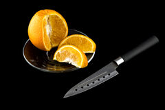 Sliced ​​orange on a transparent plate. Next to a knife Stock Image
