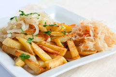 Sliced potatoes with onions and sauerkraut. On a white square plate Stock Photo