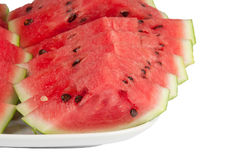 Sliced watermelon on a large plate. On a white background Royalty Free Stock Photos