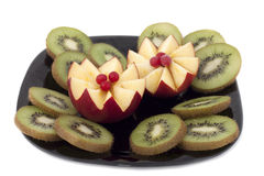 Apples and kiwi . Sliced apples and kiwi on a black plate stock images