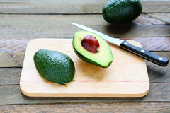 Sliced ​​avocado on wooden board stock photo
