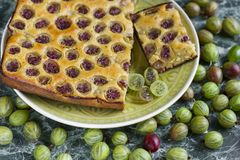 Sliced homemade pie with gooseberries on plate stock photo