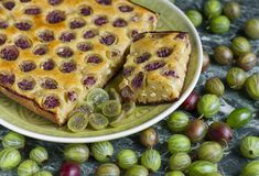 Sliced homemade pie with gooseberries on plate stock images