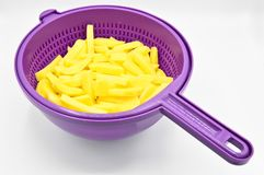 Sliced potatoes in purple plastic colander. Isolated on white background stock image