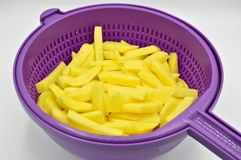 Sliced potatoes in purple plastic colander. Isolated on white background stock photography