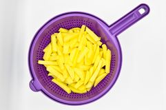 Sliced potatoes in purple plastic colander. Isolated on white background royalty free stock photos