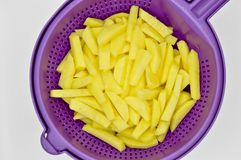 Sliced potatoes in purple plastic colander. Isolated on white background stock photo