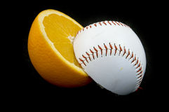 Sliced. Slices of baseball ball and orange on black background Royalty Free Stock Photo