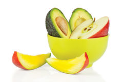 Sliced apple, avocado in ceramic cup and mango Stock Photo