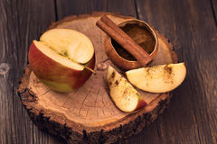Sliced apple and cinnamon. On wooden surface royalty free stock images