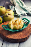 Sliced apple. Green apples and one sliced on the wooden slab Royalty Free Stock Photo