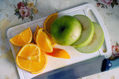 Sliced apple and orange. On a white board top view Stock Photo