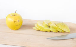 Sliced apple and a scared apple next to it with a sweet look. A scared sad apple looking at his chopped up friend on a wood board sliced with a knife royalty free stock photography