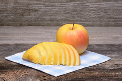 Sliced apple. On towel over wooden background Royalty Free Stock Photography