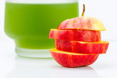 Sliced apple with vegetable juice Royalty Free Stock Images