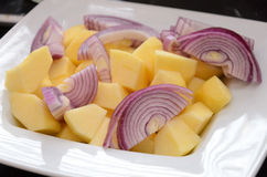Sliced apples and onions on a white plate. Filling for a Christmas goose Stock Photo