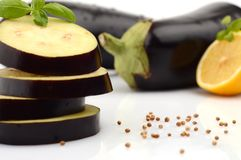 Sliced aubergine, eggplant with basil leaves and coriander seeds,lemon Royalty Free Stock Photo