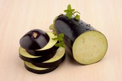 Sliced aubergine, eggplant with mint leaves on bright wooden table Stock Images