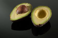 Sliced avocado on black mirror. Sliced avocado with seed on black mirror royalty free stock photography