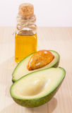 Sliced avocado and a bottle of oil. On wooden table- spa, bodycare and haircare concept Stock Photos