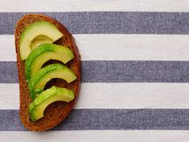 Sliced avocado on dark rye bread top view light textiles background. breakfast concept royalty free stock image
