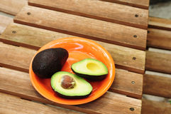 Sliced avocado on orange plate Royalty Free Stock Photography