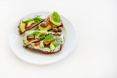 Sliced avocado on toast bread. Sandwich with cheese, tomatoes, olives and basil stock images